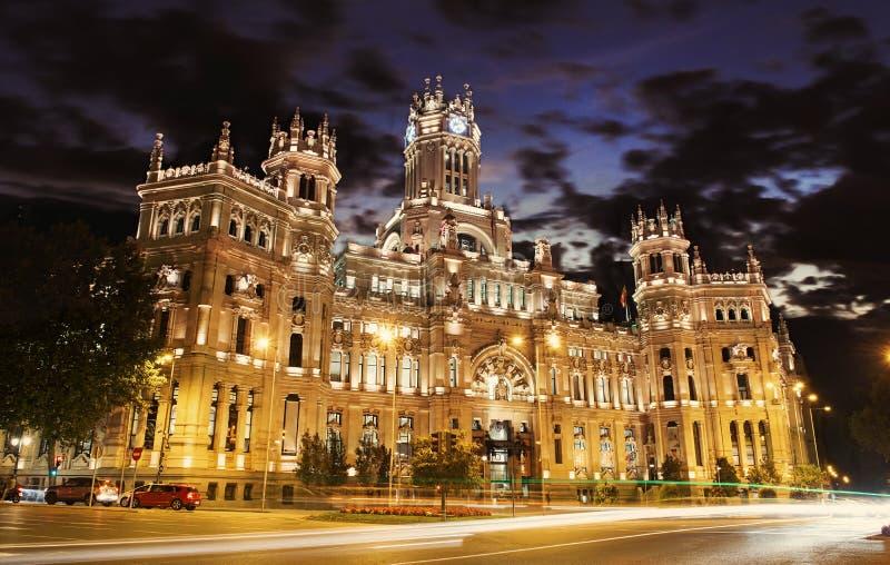 Cybele Palace på plazaen de Cibeles med ljusa slingor av trafiknatten, Madrid, Spanien arkivbilder