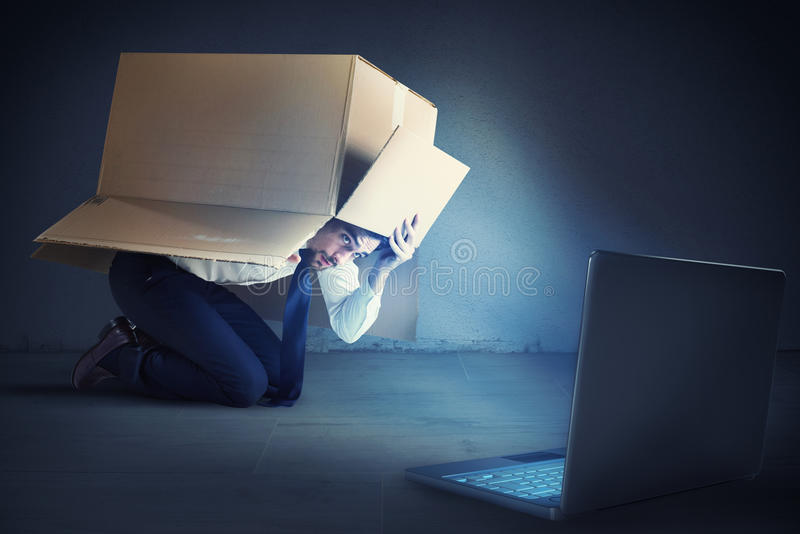 Cyber bullying. Afraid businessman hidden inside a cardboard businessman looks his laptop. Bullying on the web concept stock photos
