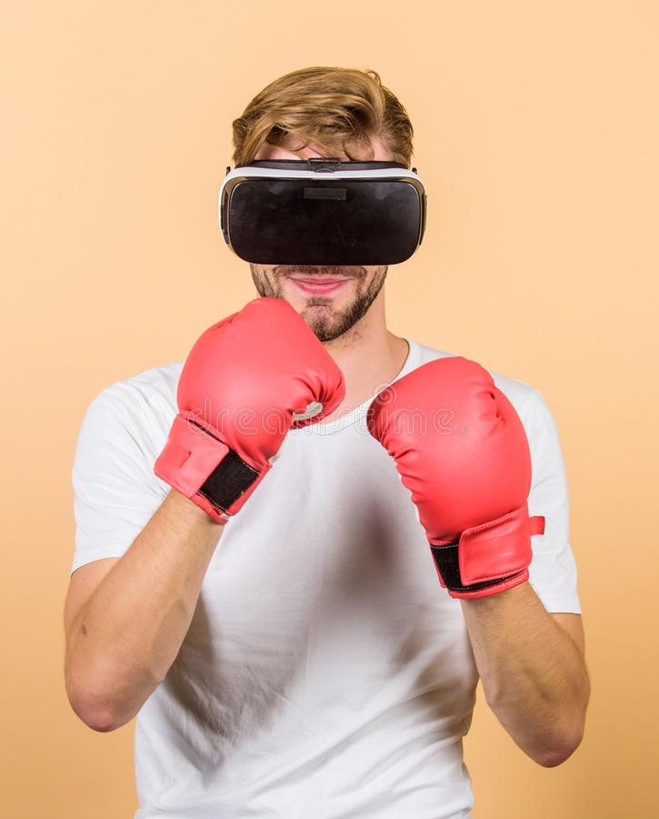 Cyber coach online training. Cyber sportsman boxing gloves. Augmented 3D world. Man boxer virtual reality headset. Simulation. Man play game in VR glasses royalty free stock photography