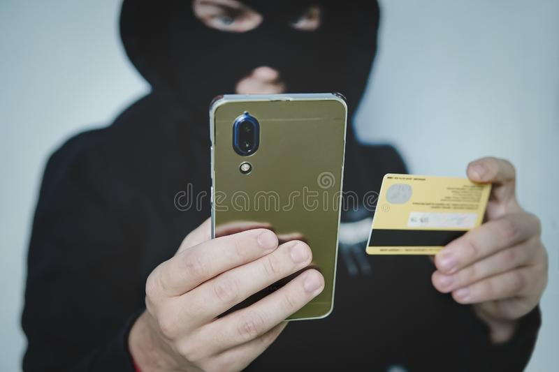 Cyber criminal in balaclava enters the information of a personal bank account. Credit card fraudulent scheme. Stealing cyber money. Using mobile. New ways of royalty free stock photography