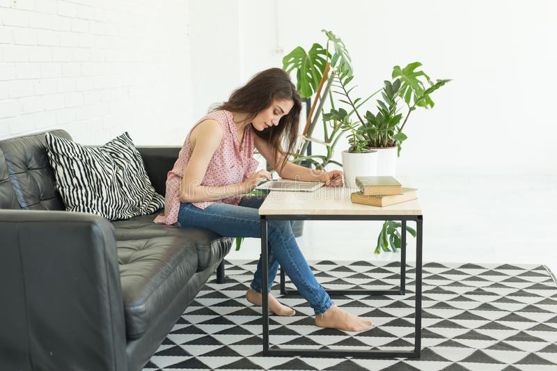 Cyber monday and black Friday concept - Young woman online shopping using tablet and credit card in livingroom royalty free stock images