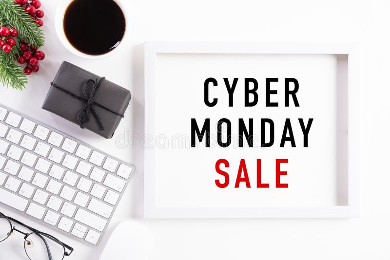 Cyber Monday Sale text on white picture frame with keyboard mouse coffee cup, gift box and Christmas tree decoration, red berries royalty free stock images