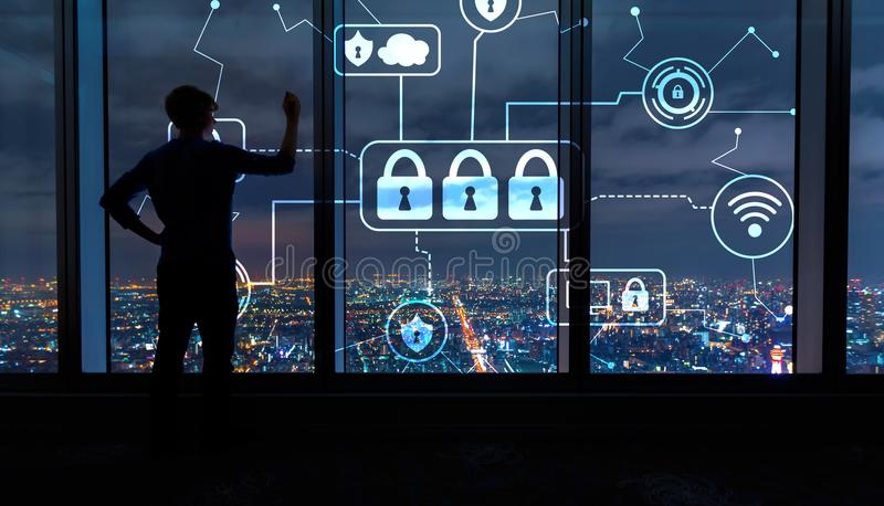 Cyber security with man by large windows at night. Cyber security with man writing on large windows high above a sprawling city at night royalty free stock images