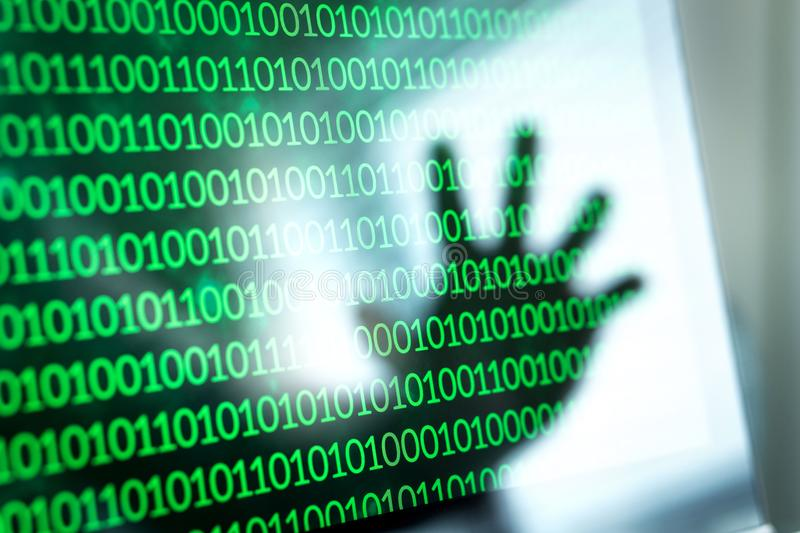 Cyber security threat and attack concept. Binary numbers, zero and one on laptop screen. Reflection of hacker hand in computer monitor