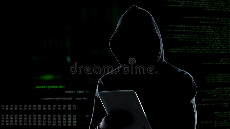 Cyberaanval met onherkenbare hakker die met een kap tabletcomputer met behulp van, cybercrime stock afbeeldingen
