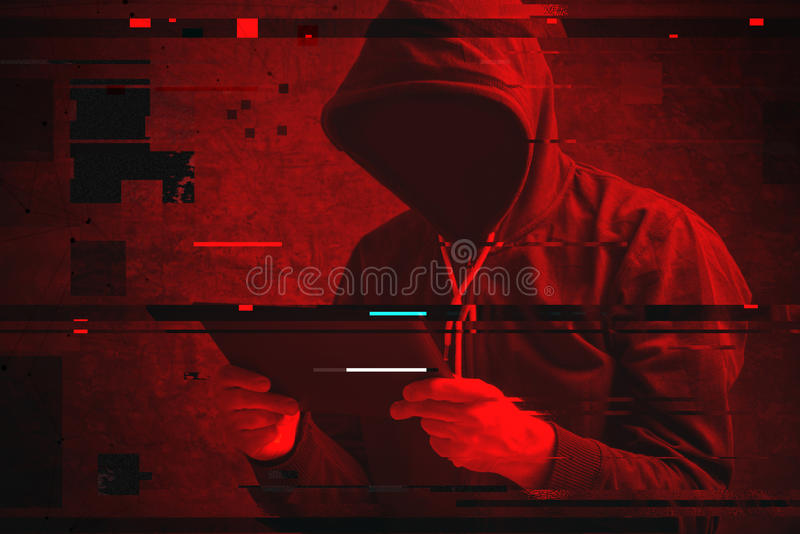 Cyberattack med den oigenkännliga med huva en hacker som använder minnestavlakomp arkivbild