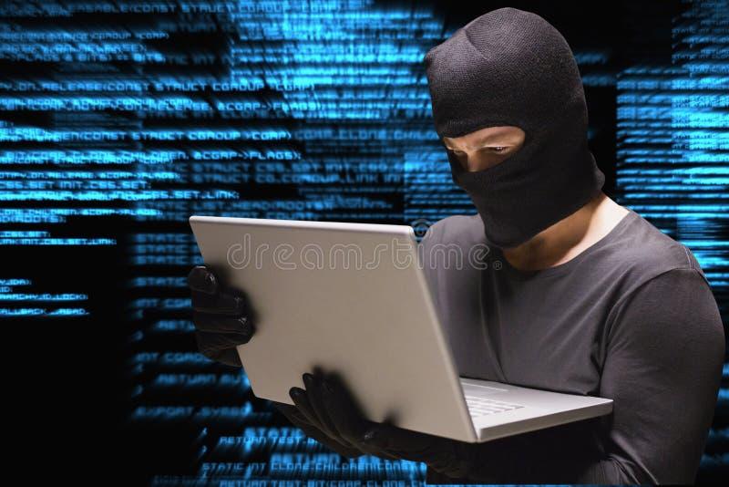 Cyberbrottslingen hackar från en bärbar dator mot bakgrund för matriskodregn arkivbilder