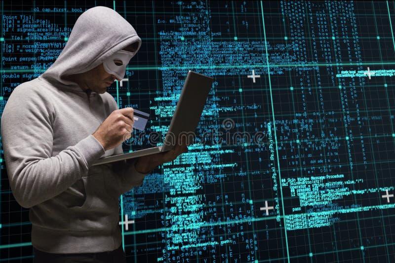 Cyberbrottslingen rymmer en kreditkort och en bärbar dator mot bakgrund för matriskodregn fotografering för bildbyråer