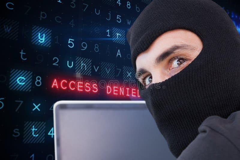Cyberbrottslingen som bär en huv, använder en bärbar dator mot websitekodbakgrund royaltyfria bilder