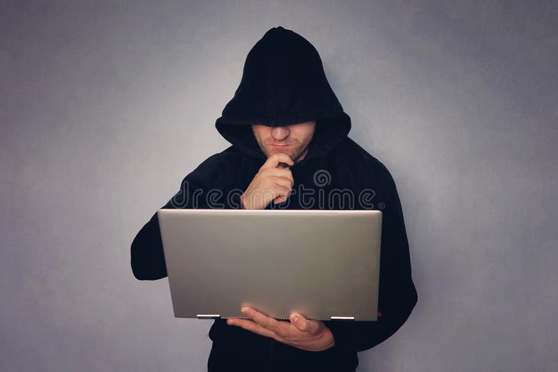 Cybercrime, έγκλημα χάραξης και τεχνολογίας - αρσενικός χάκερ στο σκοτεινό δωμάτιο με το φορητό προσωπικό υπολογιστή χάκερ σε μια στοκ εικόνες