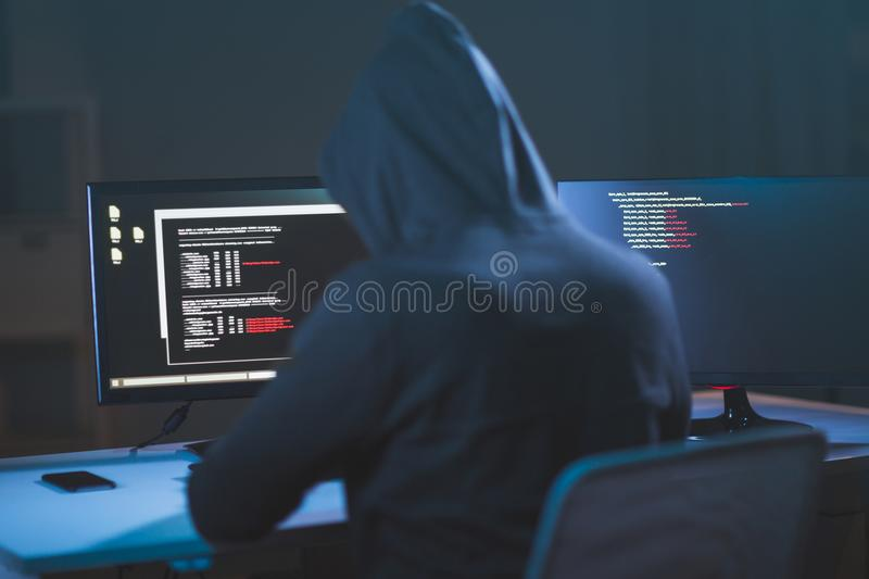 Hacker using computer virus for cyber attack. Cybercrime, hacking and technology concept - male hacker in dark room writing code or using computer virus program stock photo