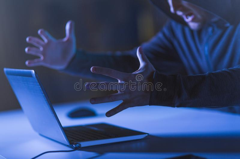 Angry hacker with laptop shouting in dark room royalty free stock image