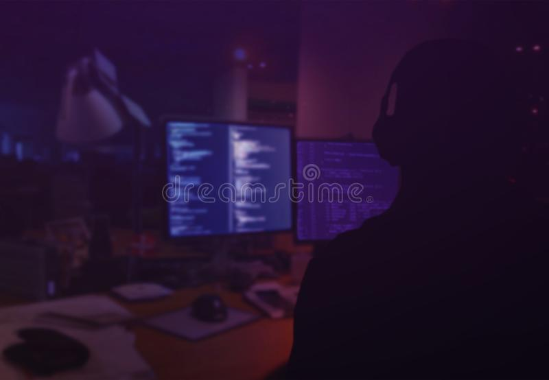 Cybercrime, hacking and technology crime concept. A hacker working in the dark stock image