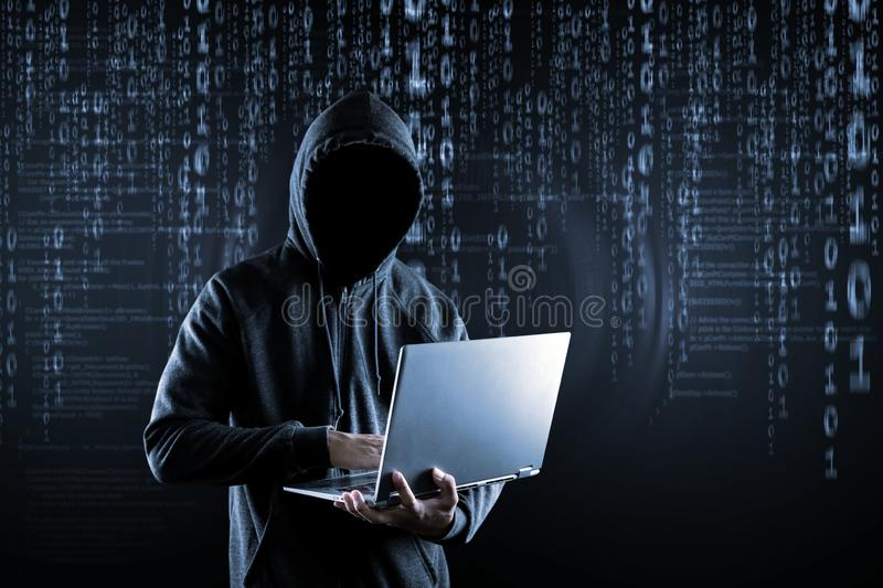 Cybercrime, hacking and technology crime. No face hacker with laptop stock image