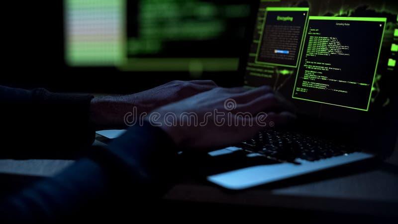 Cybercriminal som skapar ondsint programvara som skriver på bärbar datortangentbord, closeup arkivbilder