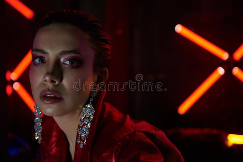 Cyberpunk close up of model wearing red bikers jacket sitting in leather sofa against neon. Cyberpunk style portrait of girl in futuristic red bikers jacket and royalty free stock images