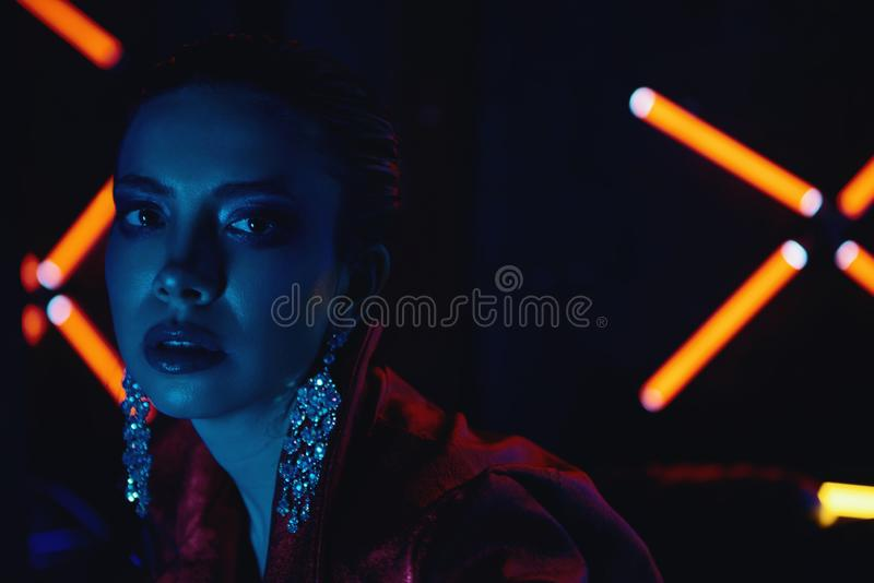 Cyberpunk close up of model wearing red bikers jacket sitting in leather sofa against neon. Cyberpunk style portrait of girl in futuristic red bikers jacket and royalty free stock photos