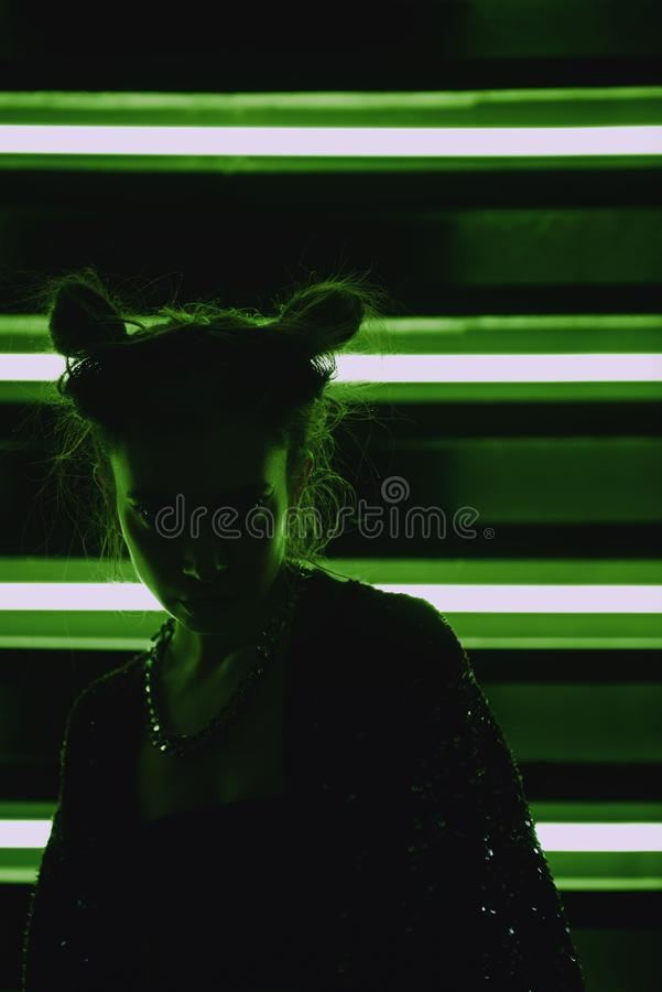 Cyberpunk close up portrait of model wearing green bathrobe with glitter against wall of neon. Cyberpunk style portrait of girl in futuristic green bathrobe with stock images