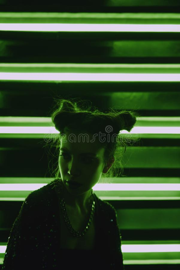 Cyberpunk close up portrait of model wearing green bathrobe with glitter against wall of neon. Cyberpunk style portrait of girl in futuristic green bathrobe with royalty free stock photography