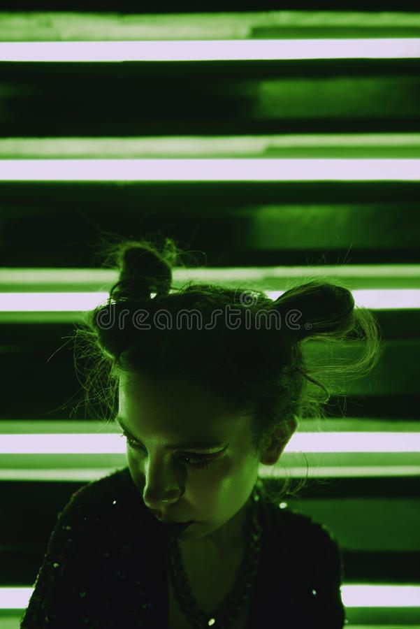 Cyberpunk close up portrait of model wearing green bathrobe with glitter against wall of neon. Cyberpunk style portrait of girl in futuristic green bathrobe with stock photos