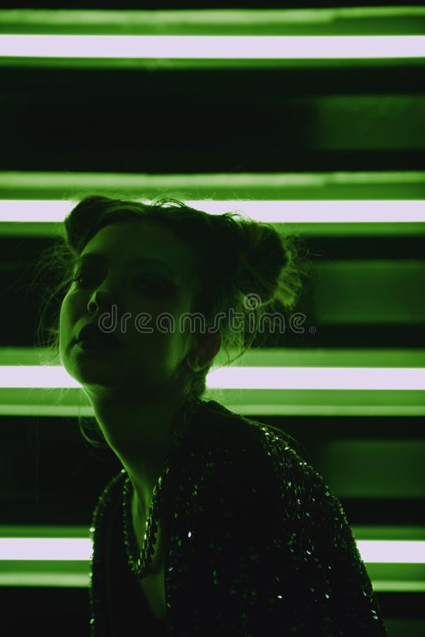Cyberpunk close up portrait of model wearing green bathrobe with glitter against wall of neon. Cyberpunk style portrait of girl in futuristic green bathrobe with stock photo
