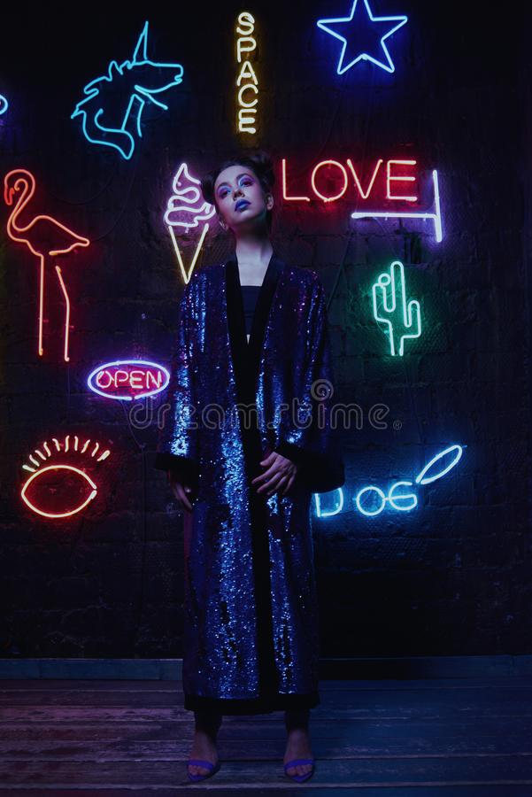 Cyberpunk shooting of model wearing bathrobe with glitter against wall of neon. Cyberpunk style portrait of girl in futuristic purple bathrobe with glitter. She stock photography