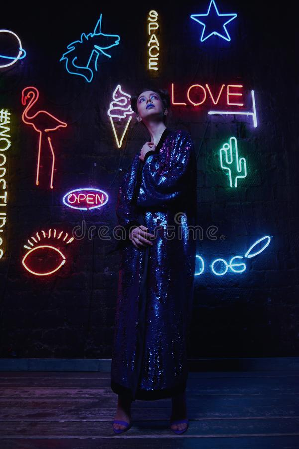 Cyberpunk shooting of model wearing bathrobe with glitter against wall of neon. Cyberpunk style portrait of girl in futuristic purple bathrobe with glitter. She royalty free stock photos
