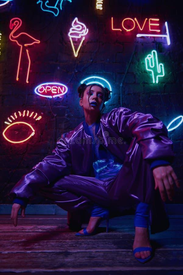 Cyberpunk shooting of model wearing contemporary sportswear against wall of neon. Cyberpunk style portrait of girl in futuristic purple sportswear. She poses stock photos