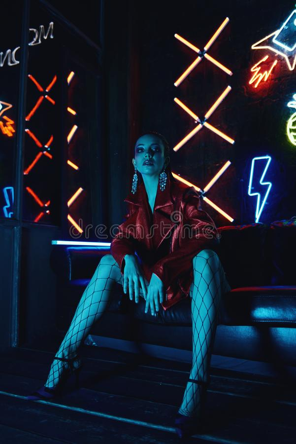 Cyberpunk shooting of model wearing red bikers jacket sitting in leather sofa against neon. Cyberpunk style portrait of girl in futuristic red bikers jacket and stock images