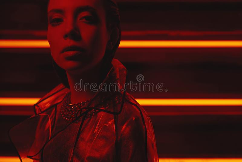 Cyberpunk shooting of model wearing transparent coat of cellophane and red dress against wall of neon. Cyberpunk style portrait of girl in futuristic coat of royalty free stock photography