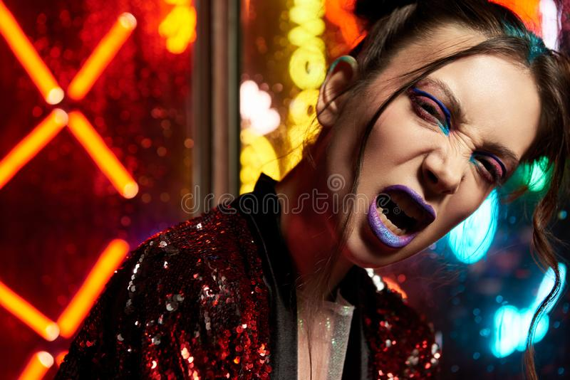 Cyberpunk style close up with model wearing red bathrobe with glitter against neon. Cyberpunk style close up beauty portrait of girl in futuristic red bathrobe royalty free stock image
