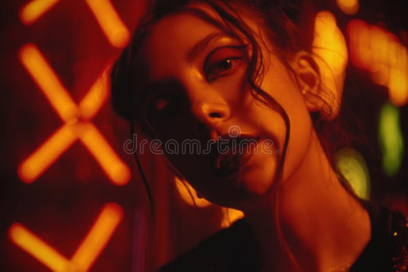 Cyberpunk style close up with model wearing red bathrobe with glitter against neon. Cyberpunk style close up beauty portrait of girl in futuristic red bathrobe royalty free stock photos