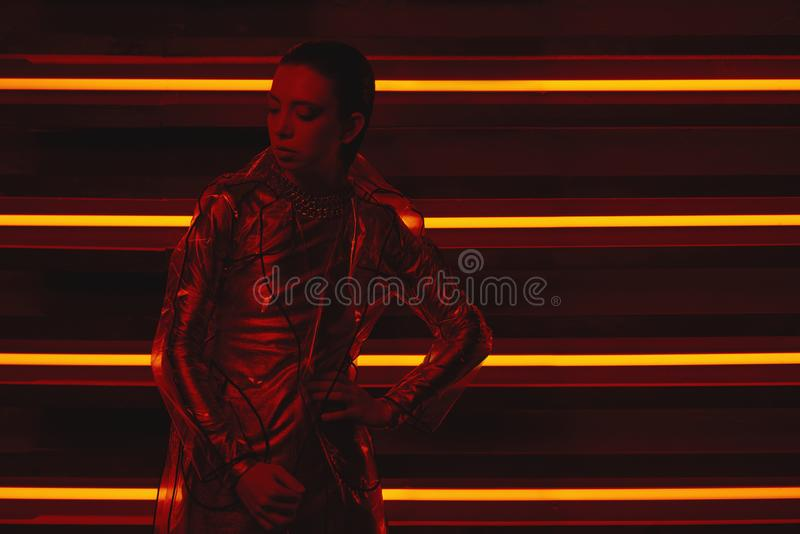 Cyberpunk shooting of model wearing transparent coat of cellophane and red dress against wall of neon. Cyberpunk style portrait of girl in futuristic coat of stock photos