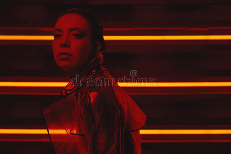 Cyberpunk shooting of model wearing transparent coat of cellophane and red dress against wall of neon. Cyberpunk style portrait of girl in futuristic coat of royalty free stock image