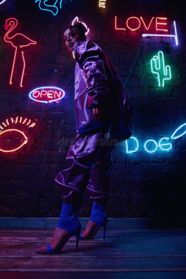 Cyberpunk shooting of model wearing contemporary sportswear against wall of neon. Cyberpunk style portrait of girl in futuristic purple sportswear. She poses stock images