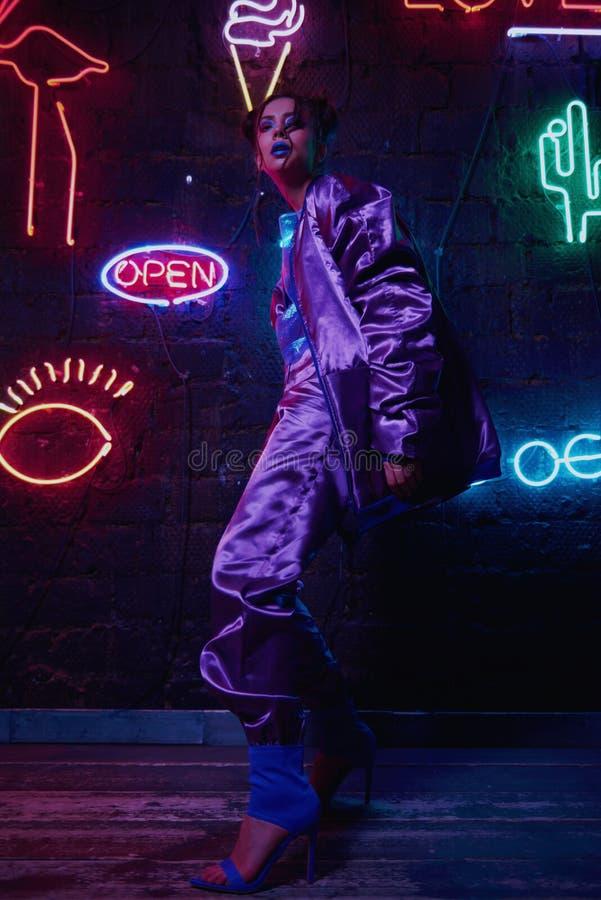 Cyberpunk shooting of model wearing contemporary sportswear against wall of neon. Cyberpunk style portrait of girl in futuristic purple sportswear. She poses stock photo