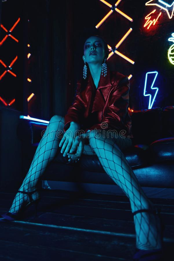 Cyberpunk shooting of model wearing red bikers jacket sitting in leather sofa against neon. Cyberpunk style portrait of girl in futuristic red bikers jacket and stock photography