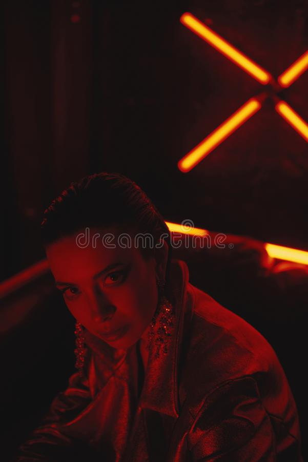 Cyberpunk close up of model wearing red bikers jacket sitting in leather sofa against neon. Cyberpunk style portrait of girl in futuristic red bikers jacket and stock images