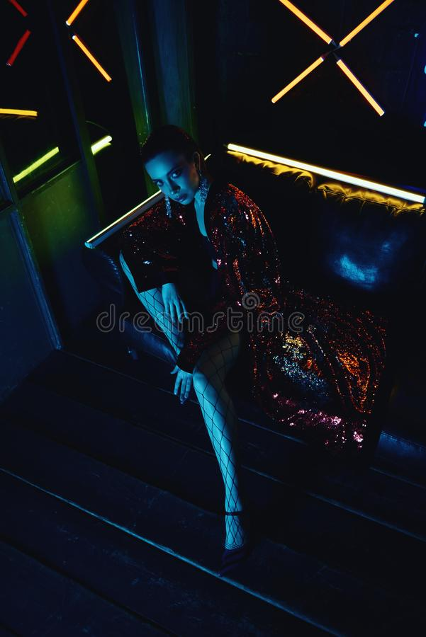 Cyberpunk shooting of model wearing red bathrobe with glitter sitting in leather sofa against neon. Cyberpunk style portrait of girl in futuristic red glittered royalty free stock photography