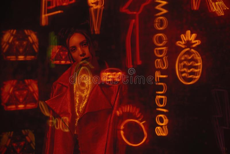 Cyberpunk style shooting with model wearing red biker jacket against the wall of TVs. Cyberpunk style shooting of girl in futuristic bikers jacket. She poses royalty free stock photo
