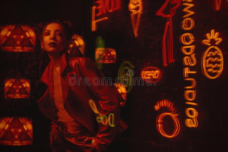 Cyberpunk style shooting with model wearing red biker jacket against the wall of TVs. Cyberpunk style shooting of girl in futuristic bikers jacket. She poses stock photos