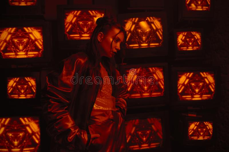Cyberpunk style shooting with model wearing contemporary sport outfit against the wall of TVs. Cyberpunk style shooting of girl in futuristic sportswear. She royalty free stock image