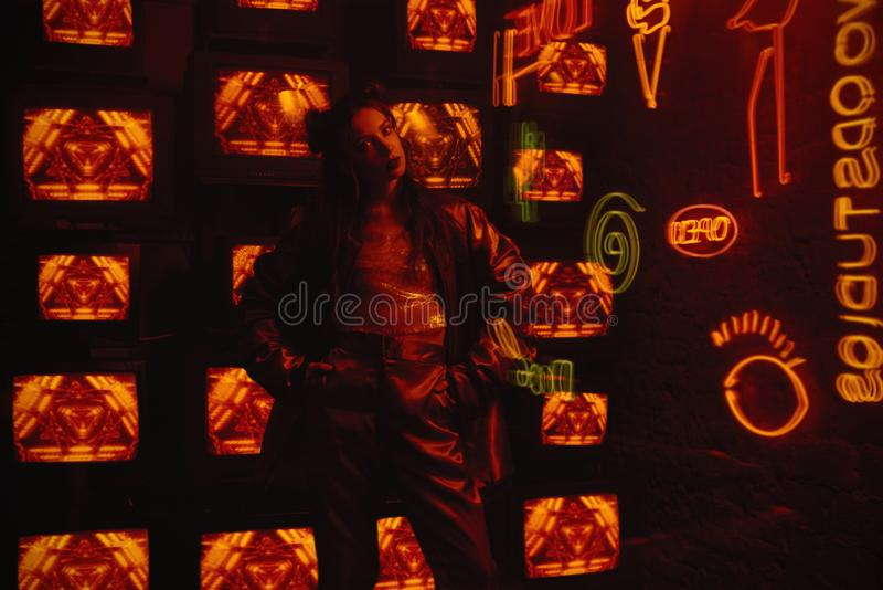 Cyberpunk style shooting with model wearing contemporary sport outfit against the wall of TVs. Cyberpunk style shooting of girl in futuristic sportswear. She stock image