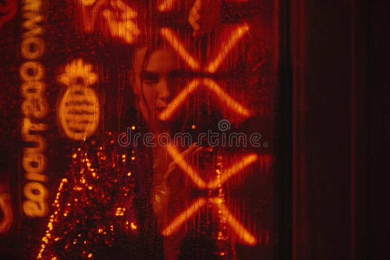 Cyberpunk style shooting with model wearing red bathrobe with glitter against neon. Cyberpunk style shooting of girl in futuristic red bathrobe with glitter. She royalty free stock photos