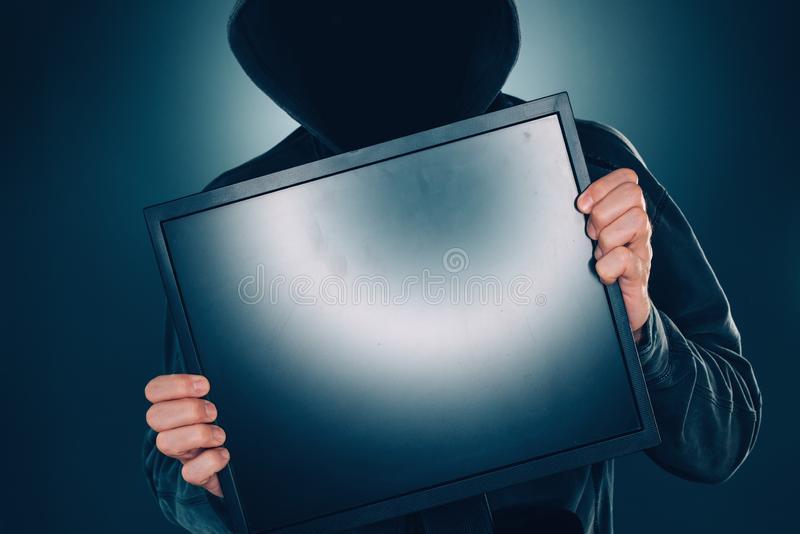 Cybersecurity, hacker de computador com os seixos vazios do monitor do computador foto de stock royalty free
