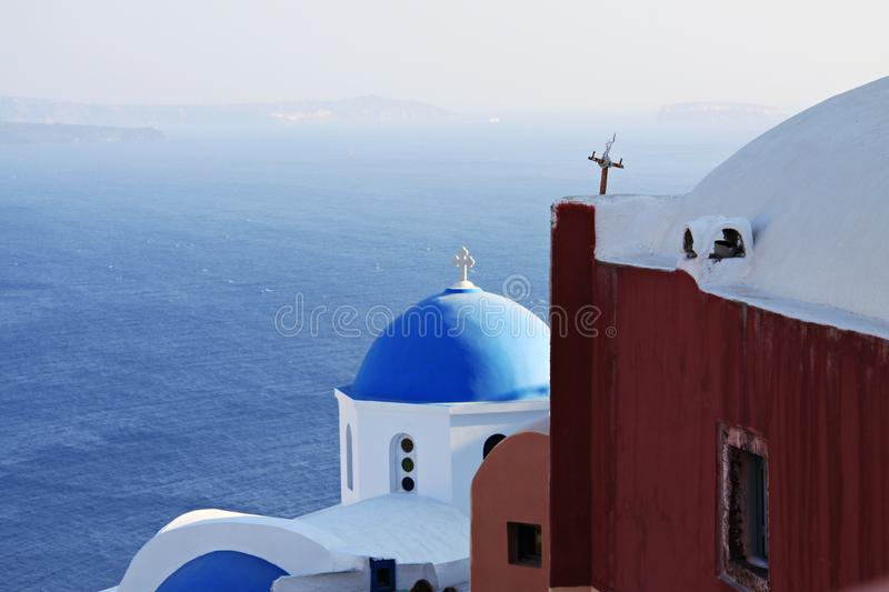 Cycladic chapel hovering over the vast blue sea. The famous blue dome of Panagia Aghion Panton church, at Oia, Santorini, from a higher viewpoint. The chapel is royalty free stock photography