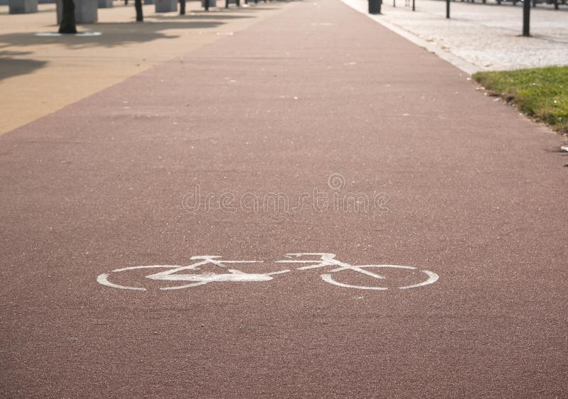 Cycle lane with painted sign. On red tarmac. Bicycle transportation path royalty free stock image