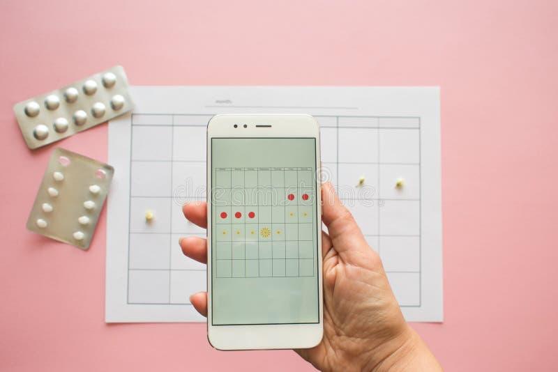 Cycle menstruel Calendrier pour le mois avec des marques et une application mobile sur l'?cran de smartphone photo stock