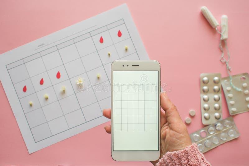 Cycle menstruel Calendrier pour le mois avec des marques et une application mobile sur l'?cran de smartphone image libre de droits