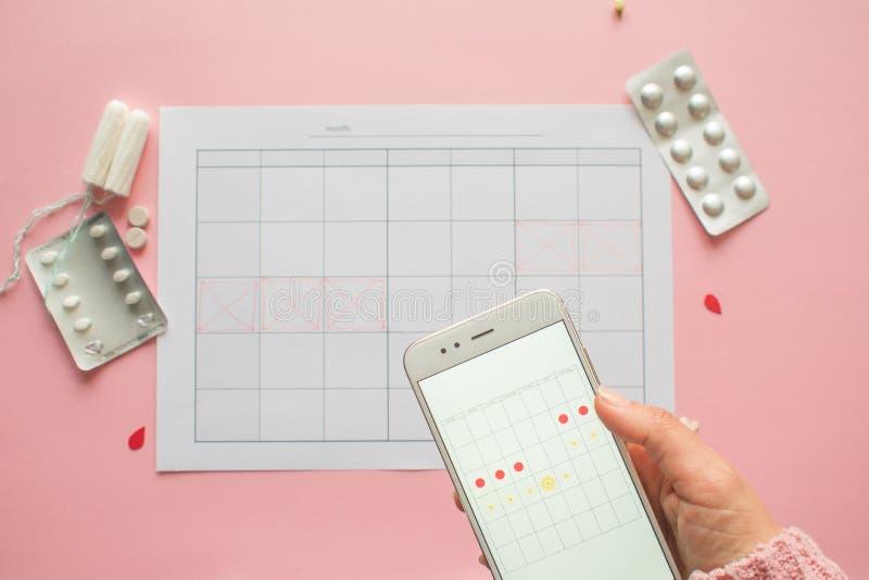 Cycle menstruel Calendrier pour le mois avec des marques et une application mobile sur l'?cran de smartphone photographie stock libre de droits